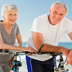 MyBenefits - Active elderly couple riding bikes at the beach